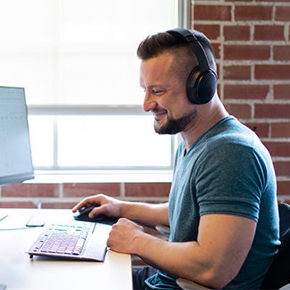 Adult sitting at their computer with headphones on smiling